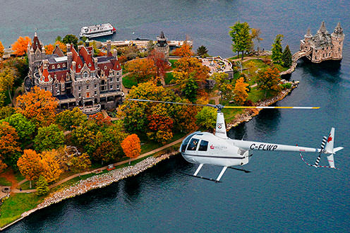 A birds eye view of a helicopter flying over Boldt Castle in the 1000 Islands. The Castle is surrounded by bright orange, red and green trees and is on the shores of the lake.