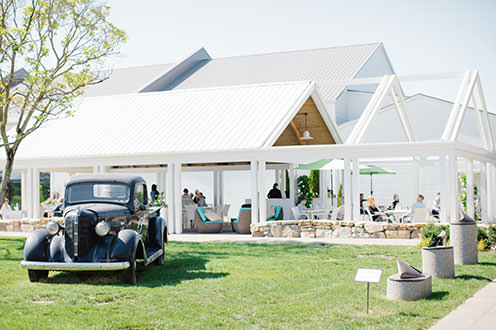 A black vintage car sits on the grass  in front of a large white open air gazebo filled with people sitting on chairs and drinking wine.