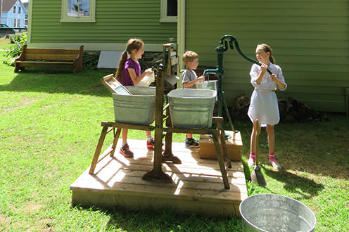 Three children filling up metal buckets with an old style water pump on a wooden platform.