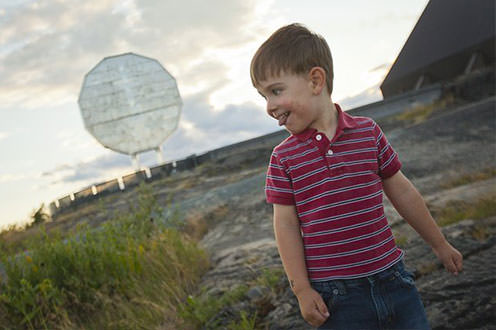 A child smiles in the foreground of the Big Nickel dominating the sky behind him