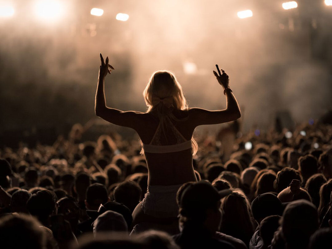 A concertgoer enjoys the view from above the crowd as she rests on her partner's shoulders.