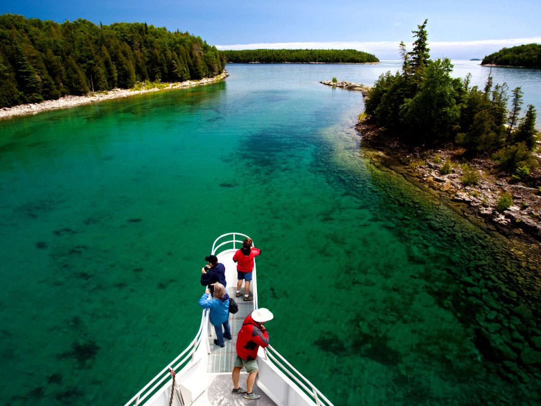 Des aventuriers profitent de la vue à la proue d'un bateau, qui glisse sur les eaux limpides du Bouclier canadien.