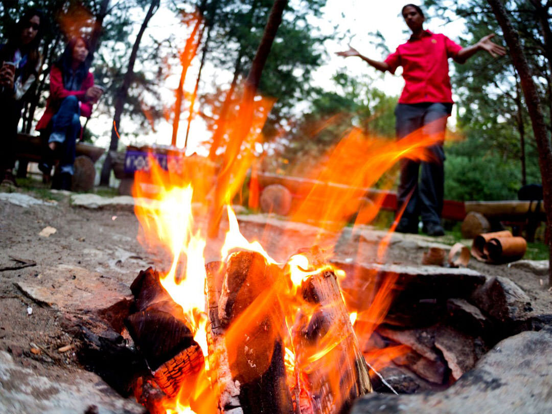 People listen to a story in background as a small fire dances front and centre.