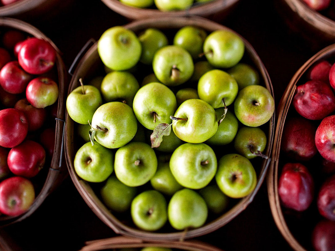 A bushel of granny smith apples rests on a market table amidst other varieties.