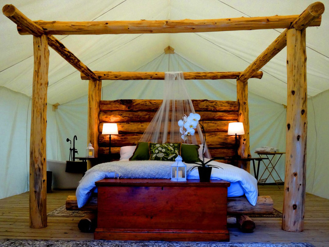 A timber-framed four-postered bed sits in the middle of a large white tent.