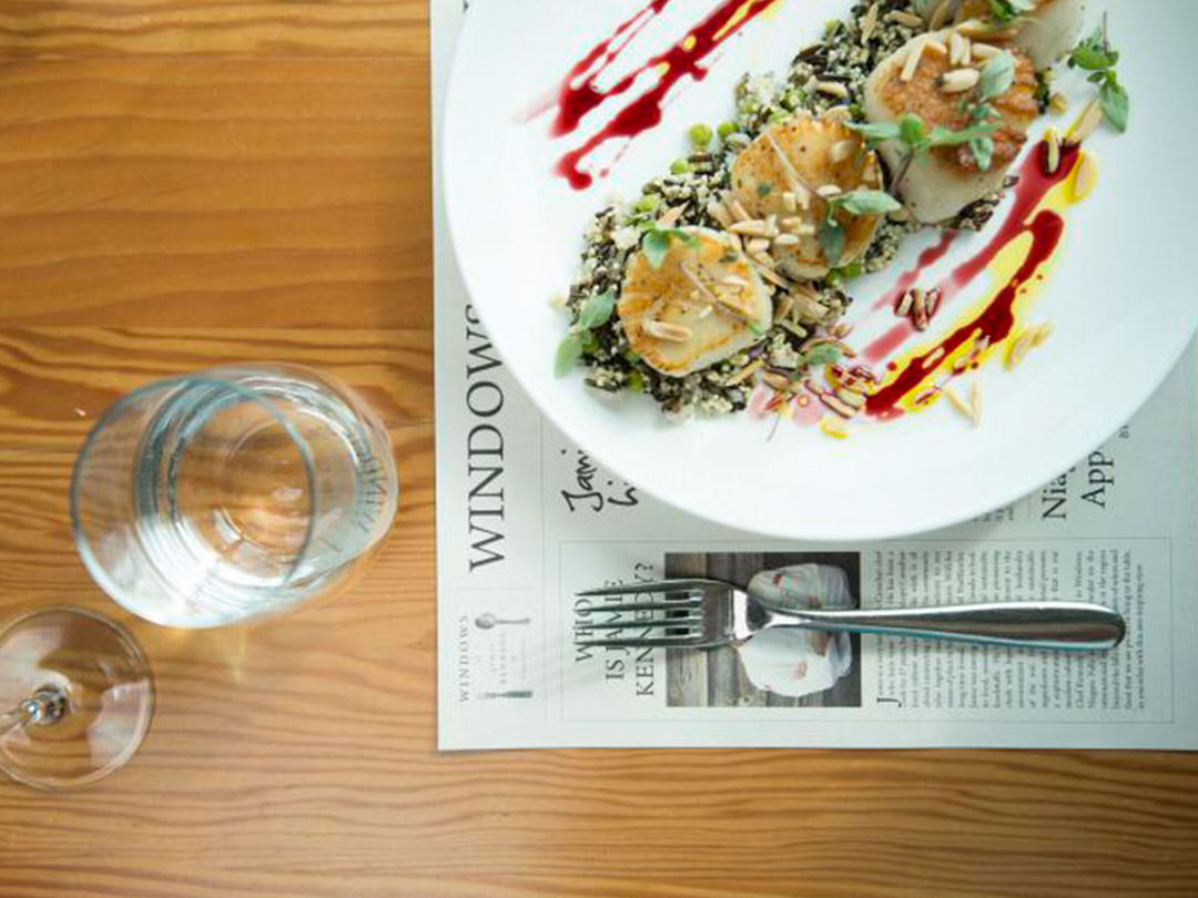 A plate of scallops awaits to be eaten beside a fork and a glass of water on a table.