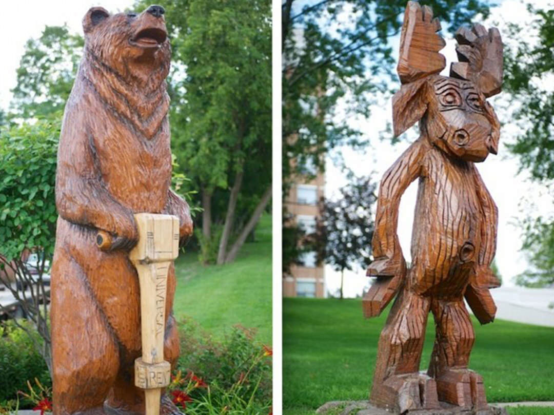 An upright woodcarved bear operating a wodden jackhammer is leftside to a smiling woodcarved moose standing on it's hind legs.