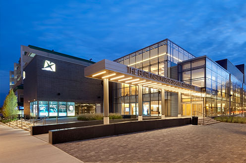 Burlington Performing Arts Centre front entrance. The large building has multiple floor to ceiling windows and stone walls.