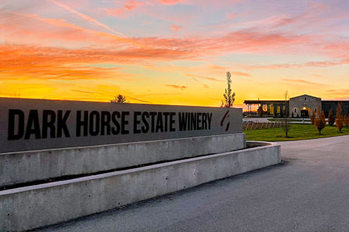 Dark Horse Estate Winery sign with the winery building in the distance during a sunset.