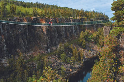 A couple stands in the middle of a suspension bridge across a wide canyon