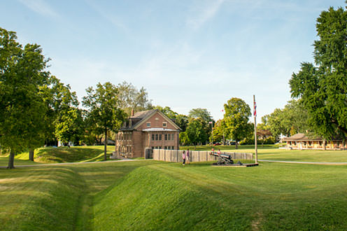 A view of Fort Malden National Historic site from across the grass. It is a a sunny day, people are walking in the distance.