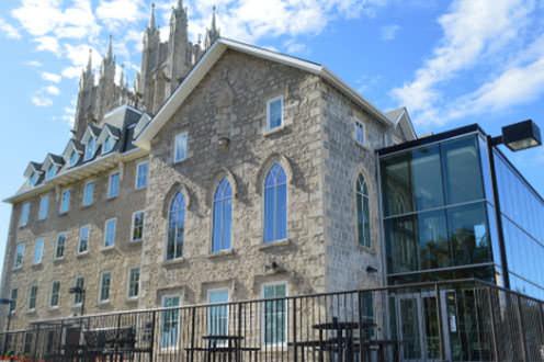 Grand couvent en pierres rénové, avec une grande extension vitrée à l'avant.