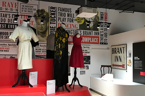 An indoor clothing exhibit at the Joseph Brant Museum. The room is filled with  mannequins styled with various  dresses. Pictures of women line the back wall along with quotes and titles from the exhibit.