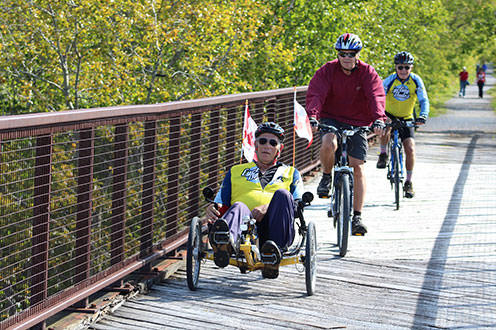 Cyclists crossing over a bridge on the Trans Canada Trail on a sunny day. There are pedestrians walking on the gravel trail in the background surrounded by lush greenery.