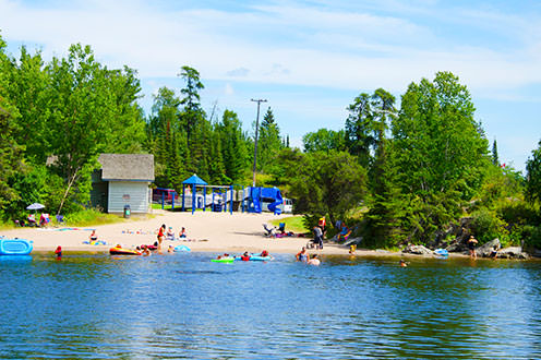 The public beach in Kenora from across the lake. There are many people enjoying the sunny day, surrounded by lush greenery. In the background there is a blue park structure and a small building.