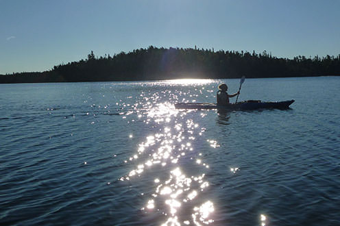 A kayaker paddling on the lake on a sunny day. The shore is in the distance and the glare from the sun shines on the lake.