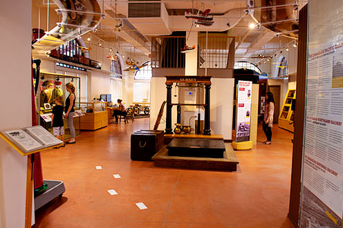 An interior view of the North Bay Museum. There information boards along the walls, a dislpay case to the left and stairs in the middle of the room. There are model planes hanging from the ceiling.