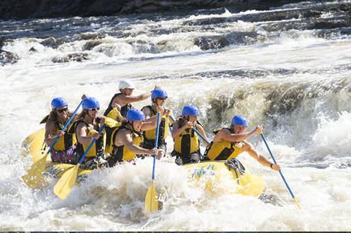 A group navigates their raft through whitewater rapids