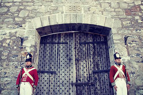 Two male soldiers dressed in War of 1812 uniforms standing on either side of a large wooden door leading into a large stone fort.