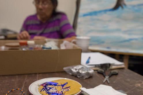 An Ojibwe artist works on crafts in a studio