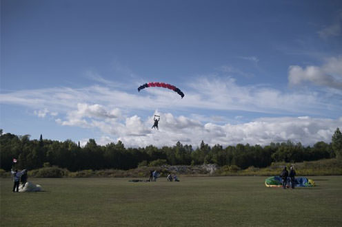 Person parachuting in open grass field