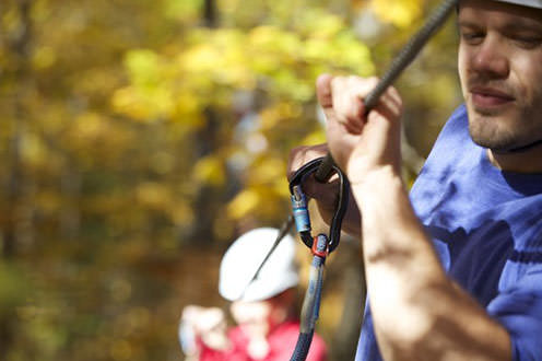 An adventurer clasps in a safety hook while ziplining through a forest