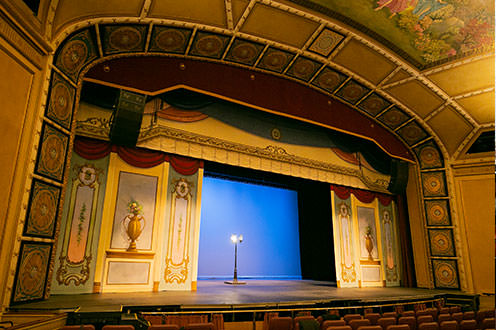 A smaller indoor theatre where the stage is surrounded with ornate tiles and paintings. A single floor lamp sits in the middle of the stage.
