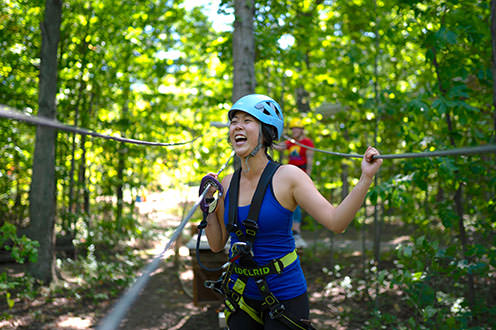 A woman wearing a harness laughs while attached to ziplines in a forest.