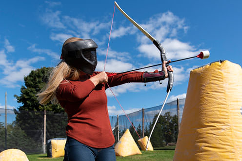 A woman with long blonde hair and full black facemask points a bow an arrow to the right in an area surrounded with black netting. The area is filled with small yellow inflatables.