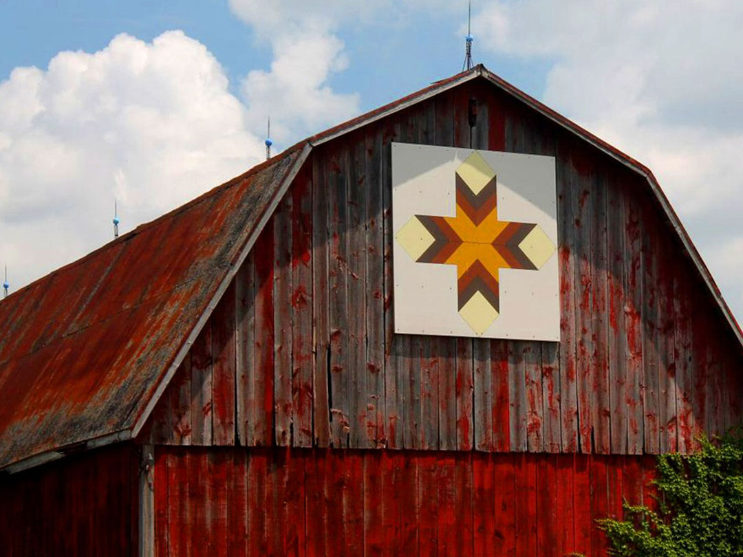 A cross-shaped quilt hangs from a barn with peeling red paint