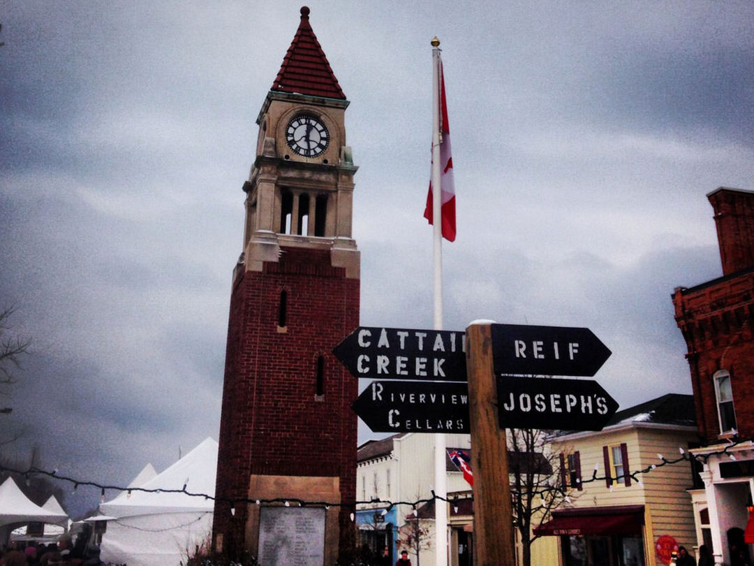 A brick clocktower and Canadian flagpole climb into the sky in a small village.