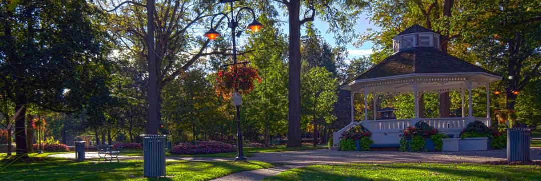 Un belvédère pittoresque en bois blanchi à la chaux est entouré de sentiers pédestres, de parterres de fleurs, de pelouses bien entretenues et d'arbres matures dans ce parc urbain.