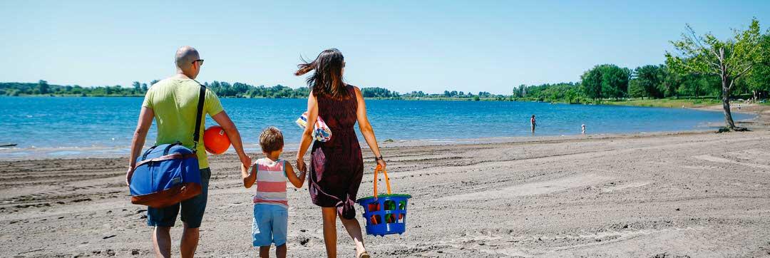 Une famille liant les mains et marchant vers une plage