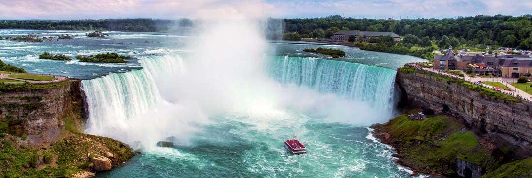 Un bateau en croisière près d'une puissante cascade