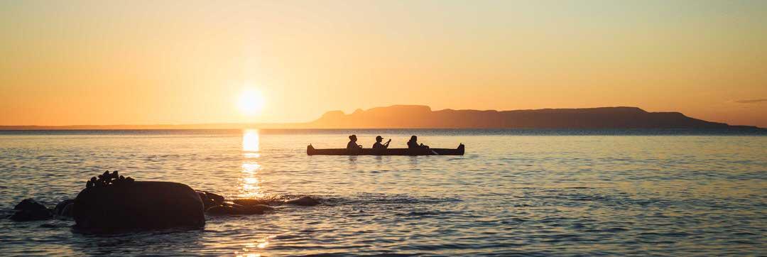Une silhouette de trois personnes pagayant un canoë au coucher du soleil