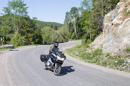 A person on a motorcycle riding along a curved road