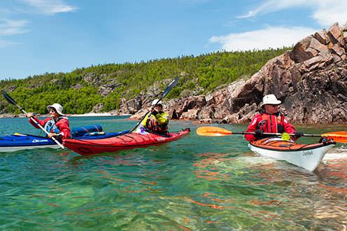 Three people in kayaks paddling on the water