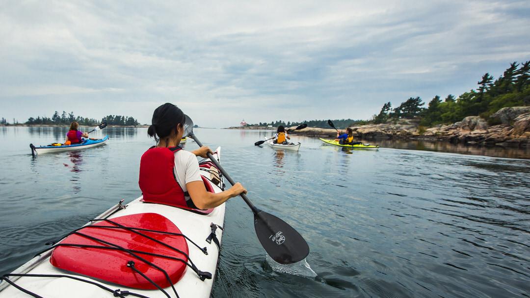 Woman paddles a sea kayak in Georgian Bay