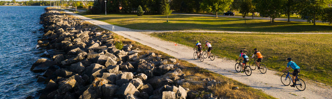 A group of five cyclists riding on a waterfront trail