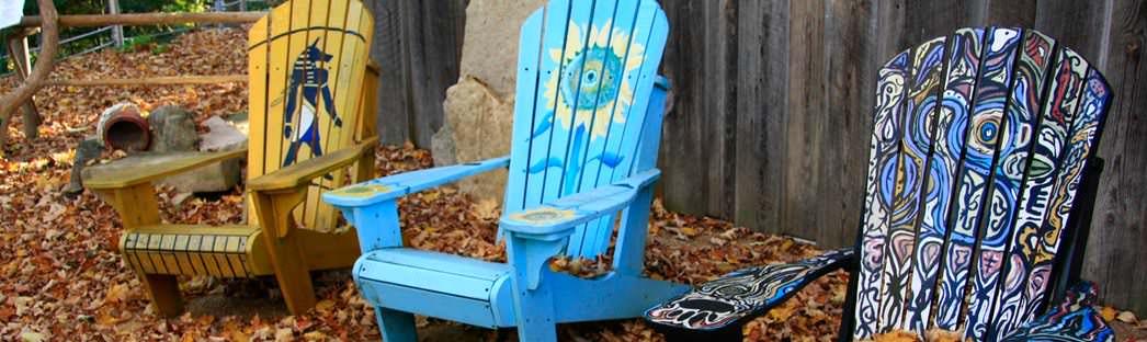 Trois chaises en bois décorées qui sont placées sur des feuilles sèches