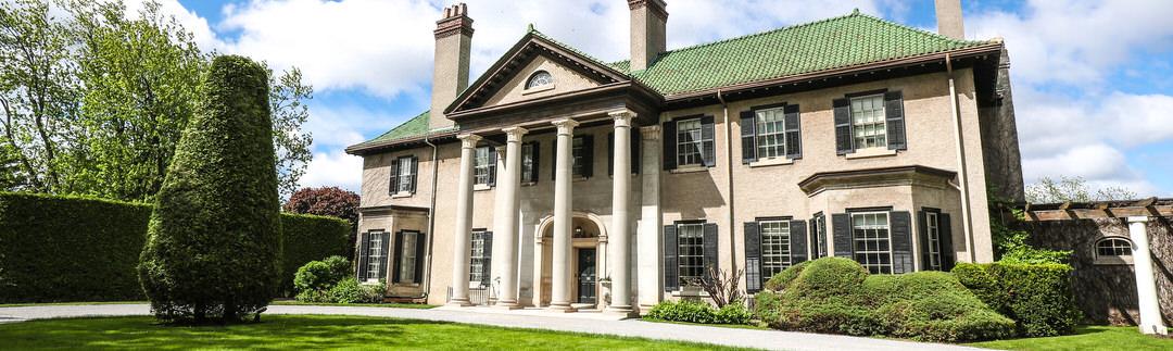 Une demeure patrimoniale majestueuse entourée de pelouse verte et de jardins
