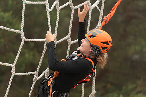 A close up of a woman wearing a helmet and a harness while grabbing onto a large net made from rope.