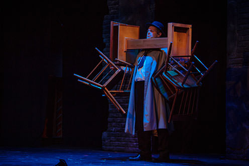 A man wearing a trench coat and hat stands with a blue spotlight shining on him. He is holding two chairs in each hand and balancing a pedestal with the chairs