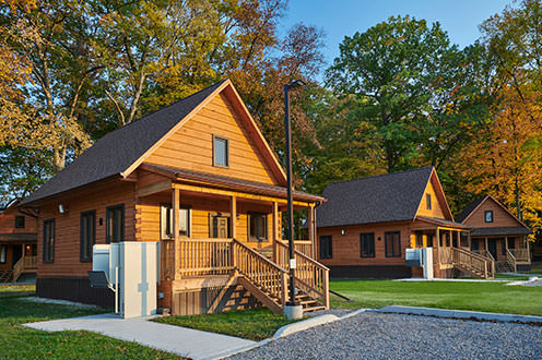 A row of newly built accessible cabins each with their own gravel parking spots and surrounded by grass and trees.