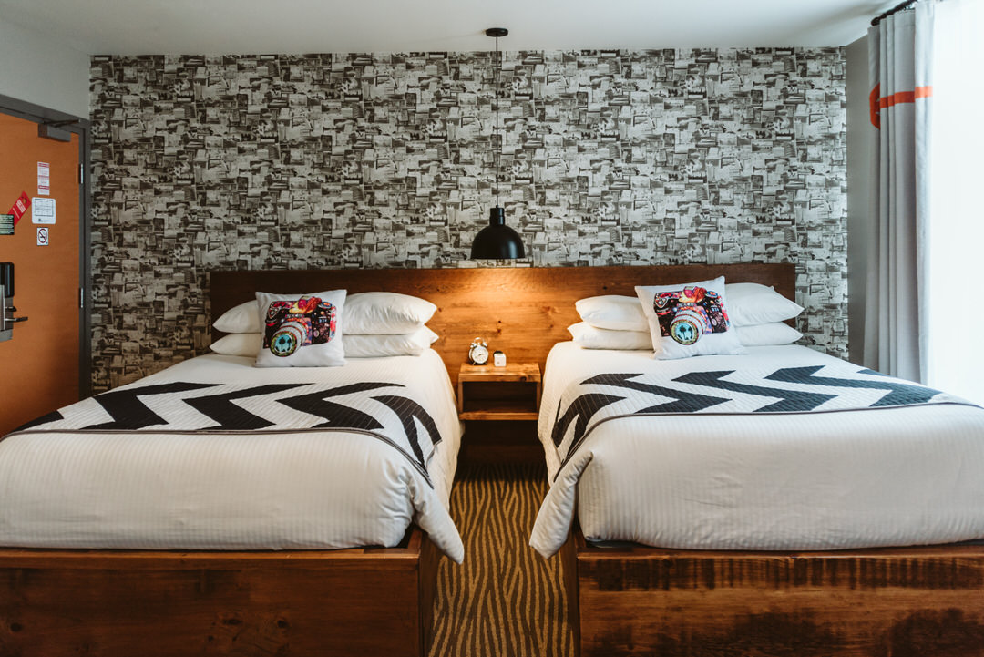 Plush bedding and soft lighting highlight the accent wall in a boutique hotel room
