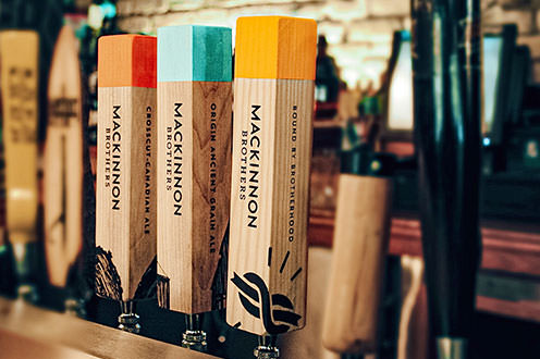 Three wooden beer taps labelled with different varieties of Mackinnon Brothers beer. Crosscut Canadian Ale, Origin Anceint Grain Ale and Bound By Brotherhood with a red, blue or yellow label