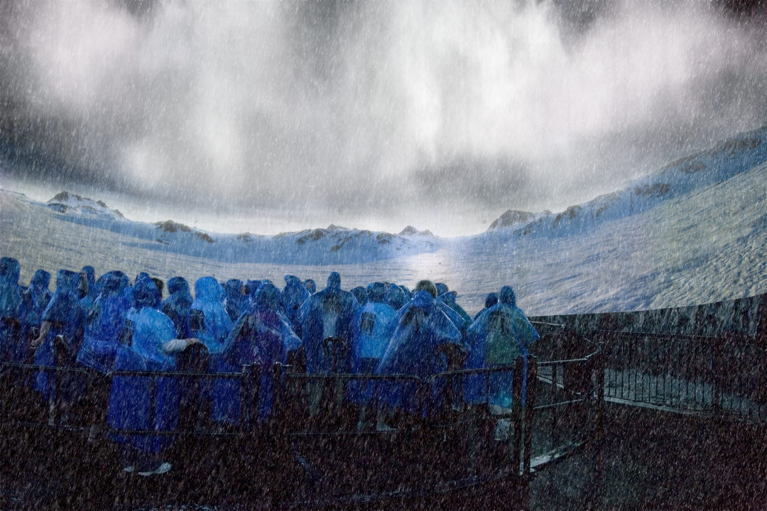 A crowd of people in rain coats in front of a movie screen
