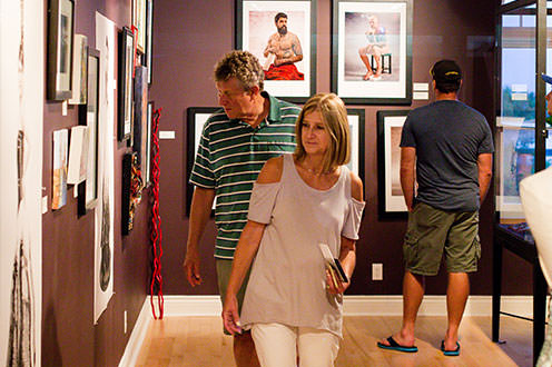 A man and a woman looking at the art displayed on the wall of an art gallery. Another man is shown in the background looking at art.