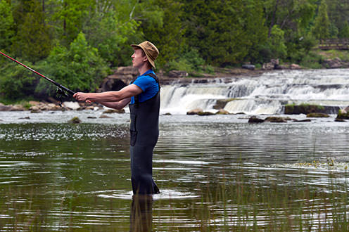 A man wearing waders on the shores of a lake is casting a fishing rod. There is a waterfall in the distance.
