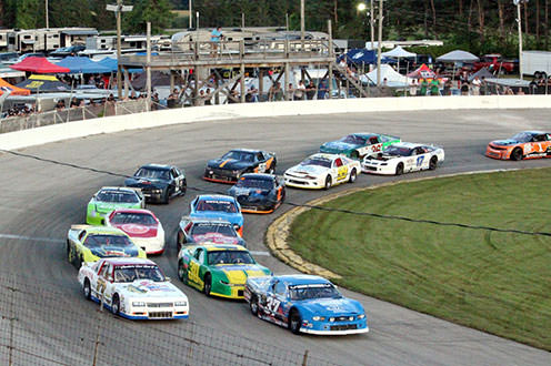 Fifteen race cars speeding around the bend of an oval racetrack. There are tents in the background as well as a spectators standing on a wooden observation deck.